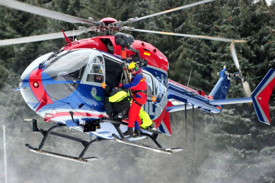 in Retter der Bergwacht Thüringen hängt mit einem verletzten Skifahrer an einem Helikopter der Thüringer Polizeihubschrauberstaffel (Archivfoto).