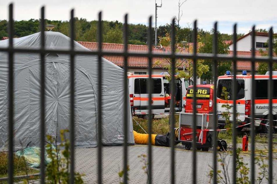 Fahrzeuge vom Katastrophenschutz, DLRG und dem Deutschen Roten Kreuz stehen auf dem Gelände der Bundespolizei in Frankfurt (Oder) neben einem Zelt, in dem eingeschleuste Menschen betreut werden.