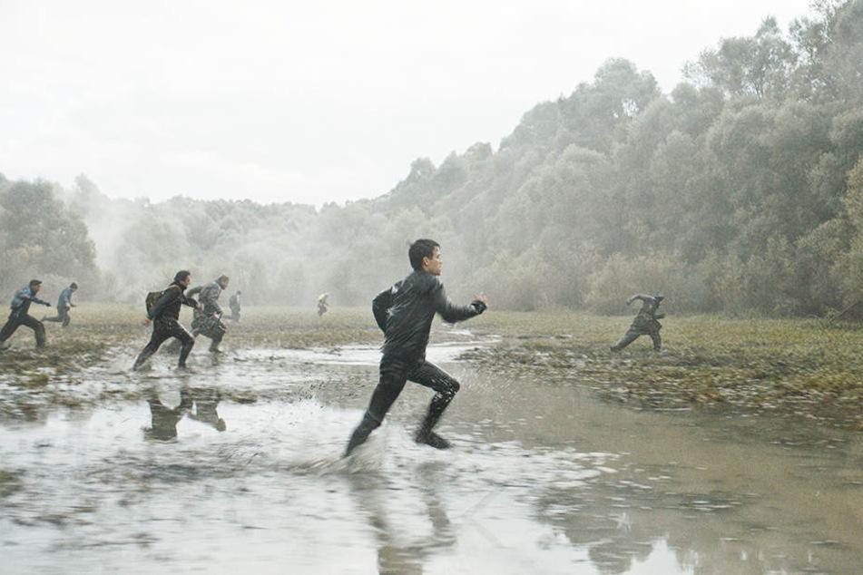 Aryan Dashni (Zweiter von r., Zsombor Jeger) flüchtet durchs Wasser in einen Wald, um den ungarischen Grenzsoldaten zu entgehen.