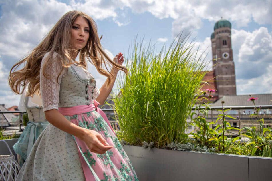 Cathy Hummels steht im selbst designten Dirndl vor der Münchener Frauenkirche auf einem Dachgarten.