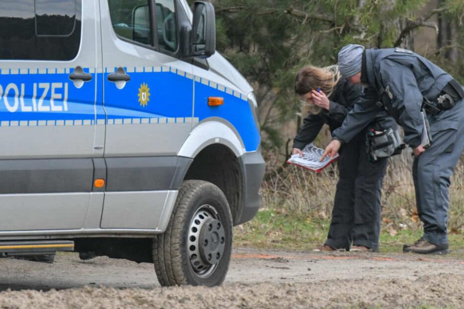 Beamte bei der Suche an einem Waldgebiet in Brandenburg.