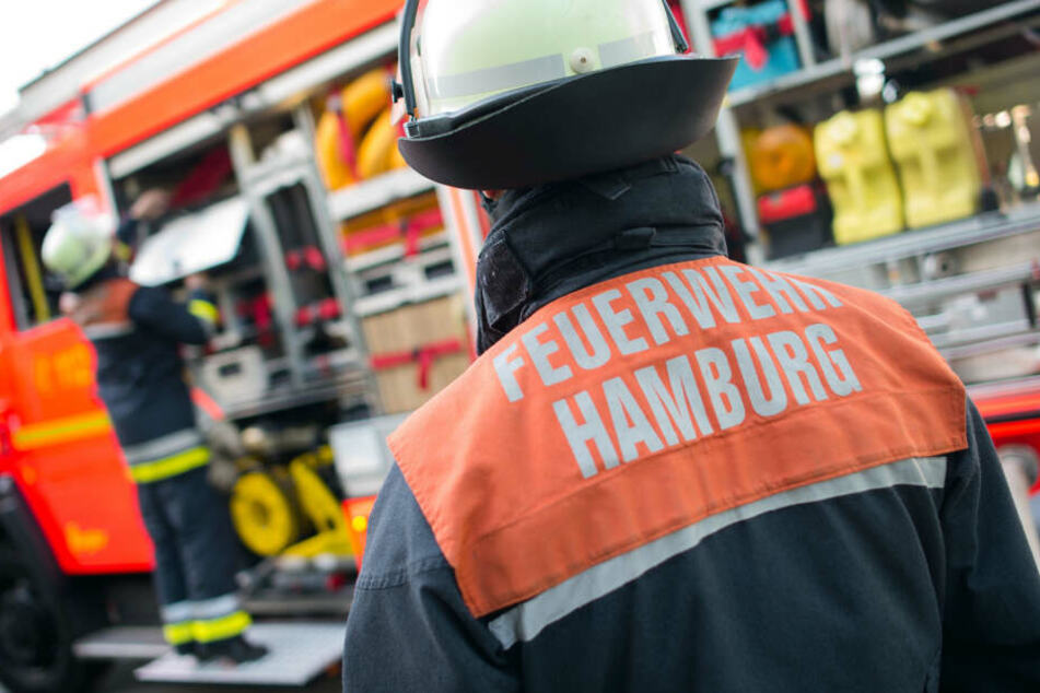 Ein Feuerwehrmann der Hamburger Feuerwehr steht während einer Übung an einem Löschfahrzeug. Am europaweiten Tag des Notrufs will sich die Hamburger Berufsfeuerwehr am Montag besonders transparent auf Twitter zeigen.