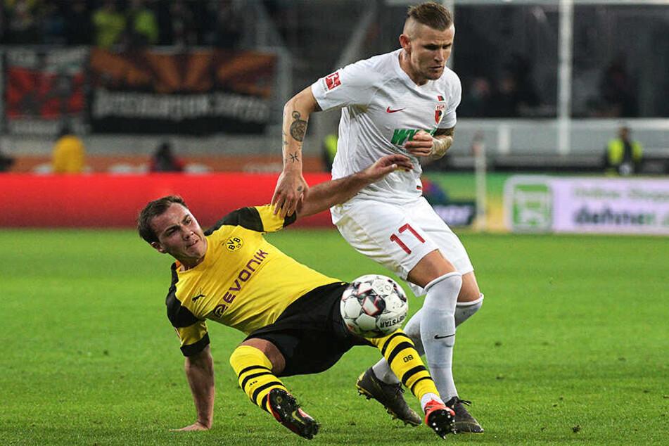Voller Einsatz: Augsburgs Jonathan Schmid (r.) und Mario Götze von Dortmund kämpfen um den Ball.