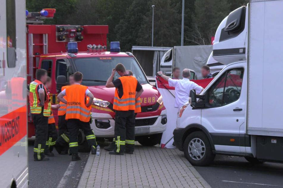 Rettungskräfte stehen an der Unglücksstelle.