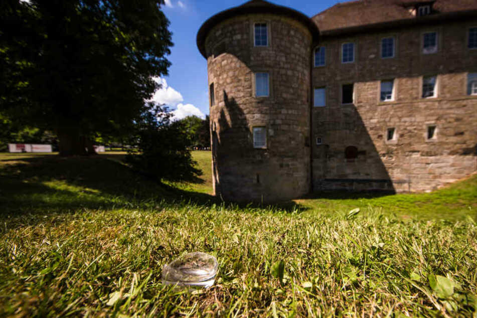 Der Boden einer zerbrochenen Glasflasche liegt im Park vor dem Burgschloss auf einer Wiese.