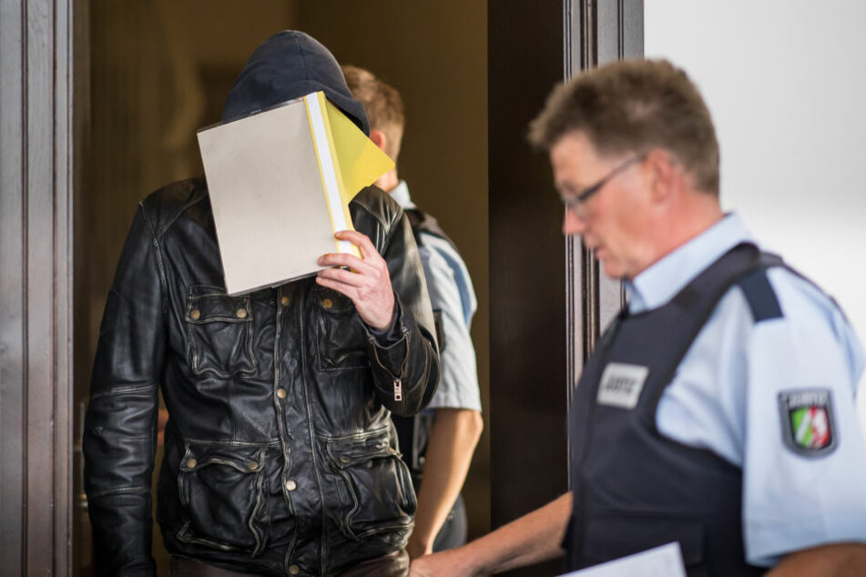 Der Angeklagte Alfred P. wird beim Prozessauftakt im Landgericht in Paderborn von zwei Justizbeamten in den Sitzungssaal geführt.