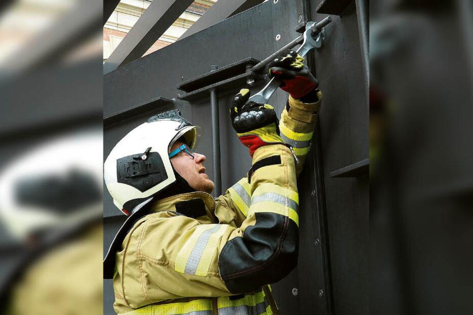 Mit einem großen Schraubenschlüssel macht dieser Feuerwehrmann eines der Flutschutztore hochwasserfest.