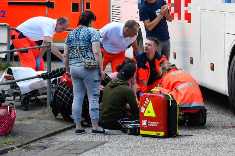 Ersthelfer kümmern sich um das Kind, das von dem Bus erfasst wurde.