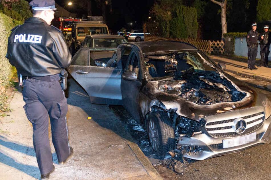 Ein Polizeibeamter begutachtet das durch die Flammen zerstörte Fahrzeug.