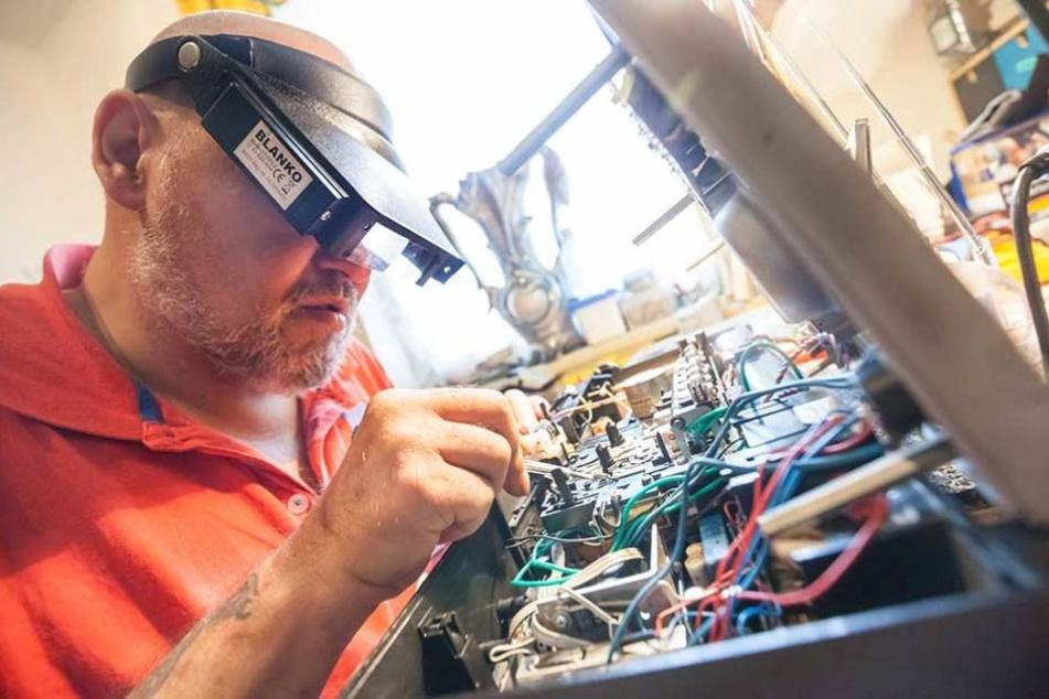 André Bethke (53) repariert mit Kopflupe einen Radiorecorder aus DDR-Zeiten. Mehr als 70 Geräte hat er zu Hause.