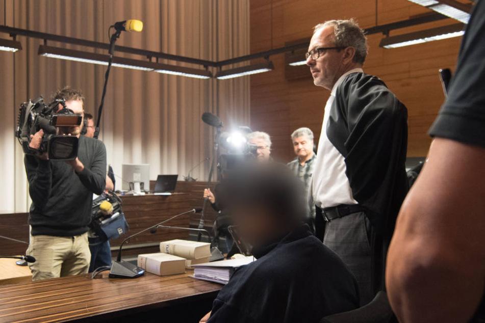 Der Angeklagte Hussein K. mit Handschellen im Landesgericht Freiburg.
