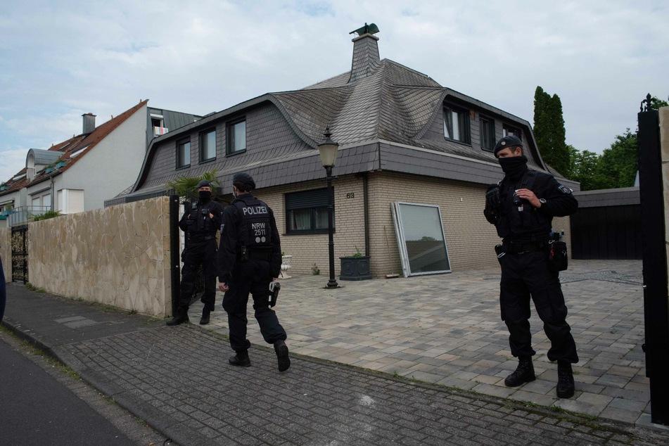 Polizisten bewachen das aus in dem eine Razzia stattgefunden hat.