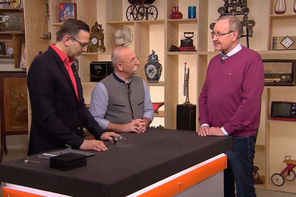 Göst Thomsen (r.) zeigt Hort Lichzer (m.) und Experte Detlev Kümmel (l.) den Lego-Stein.