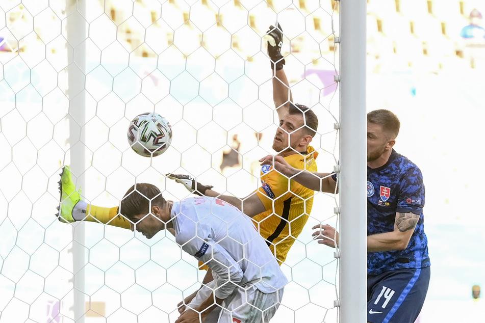 Slowakei-Torwart Martin Dubravka (M.) wird unter Druck gesetzt und boxt das Leder zum 1:0 für Spanien ins eigene Tor.