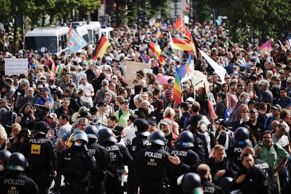 Teilnehmer einer Demonstration gegen die Corona-Maßnahmen stehen auf der Straße des 17. Juni.