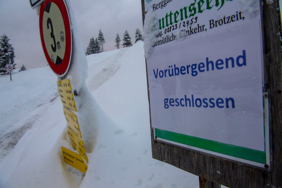 """Ein Hinweisschild auf einen Gasthof mit der Aufschrift """"Vorübergehend geschlossen"""" steht neben einem Weg im Skigebiet Kranzberg oberhalb von Mittenwald."""