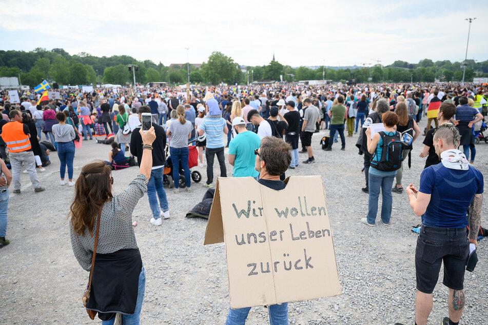 """Ein Mann steht während einer Protestkundgebung der """"Initiative Querdenken 711"""" mit einem Schild, auf dem """"Wir wollen unser Leben zurück"""" steht, auf dem Cannstatter Wasen."""