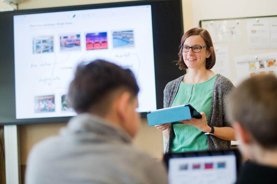 Eine Lehrerin steht mit einem iPad vor einer digitalen Schultafel.