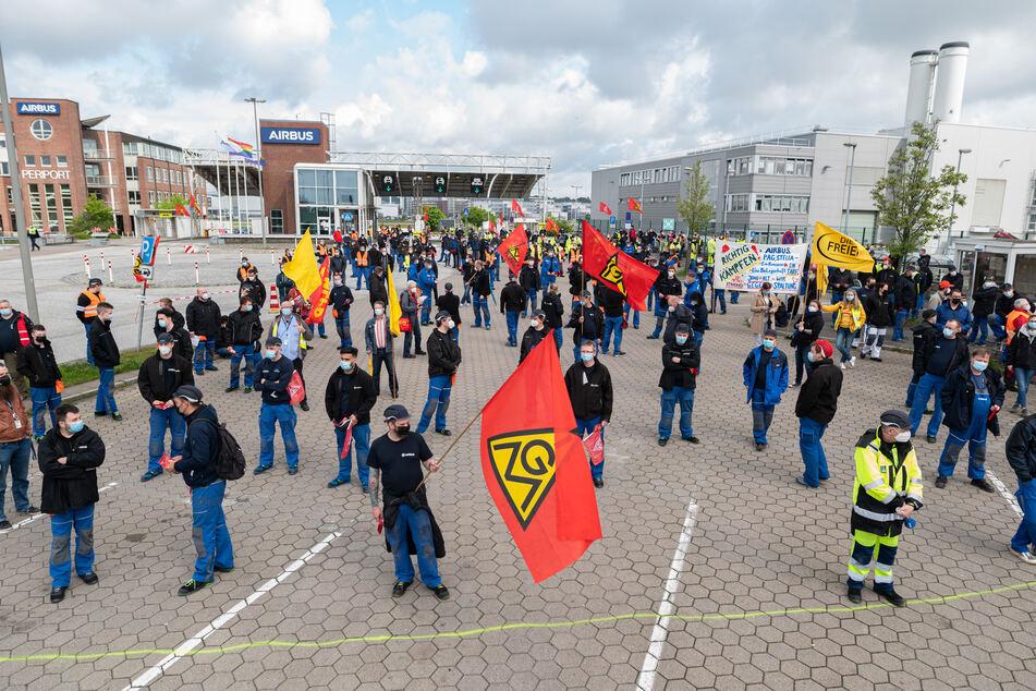 Beschäftigte des Airbus-Werkes in Hamburg-Finkenwerder stehen vor den Toren des Werksgeländes: Es droht ein neuer Warnstreik. (Archivbild)