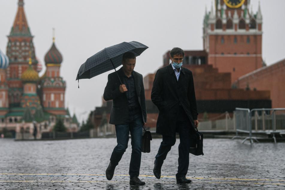 Moskau: Menschen gehen bei Regen über den Roten Platz.