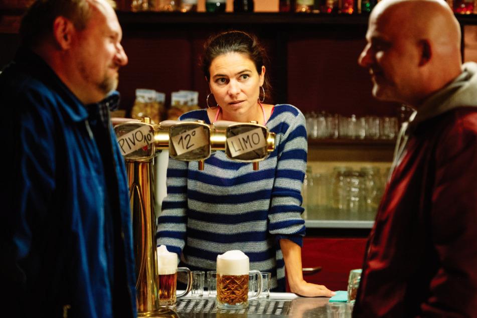 Vandam (r., Hynek Cermak) steht auf die verschuldete Kneipeninhaberin Lucka (M., Katerina Janeckova) und verteidigt sie gegen Männer, die sie anflirten.