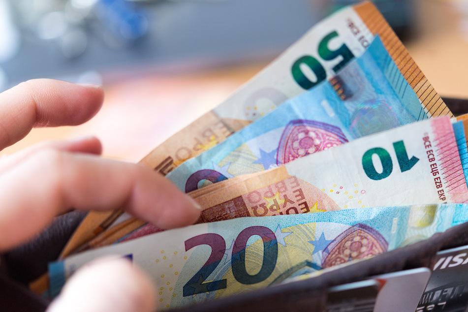 Eine Frau hält eine Geldbörse mit Banknoten in der Hand.