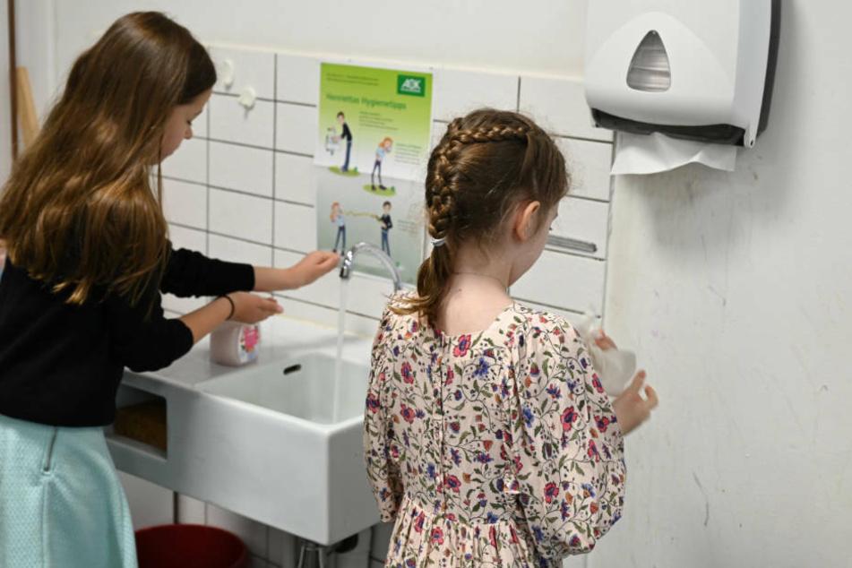 Zwei Schülerinnen der Klasse 4b der Wiesbadener Robert-Schumann-Grundschule waschen ihre Hände vor Unterrichts-Beginn.