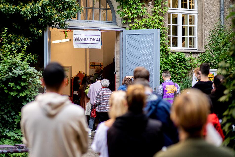 Etliche Menschen stehen z. B. in Prenzlauer Berg vor einem Wahllokal an, um ihre Stimmen abzugeben.
