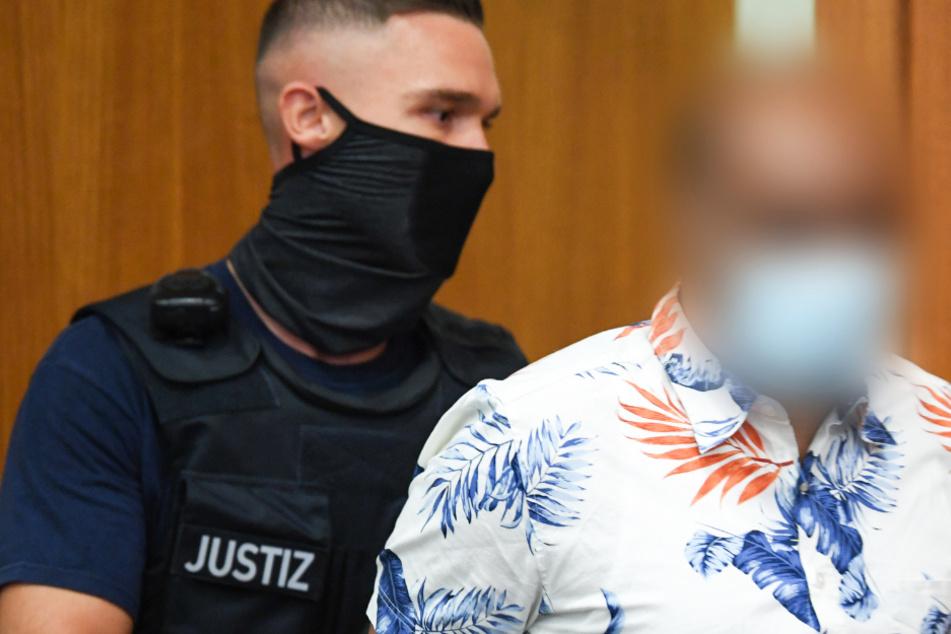 Ein Justizbeamter führt den 41-jährigen Angeklagten (r) zum Prozessauftakt in den Gerichtssaal des Frankfurter Landgerichts.