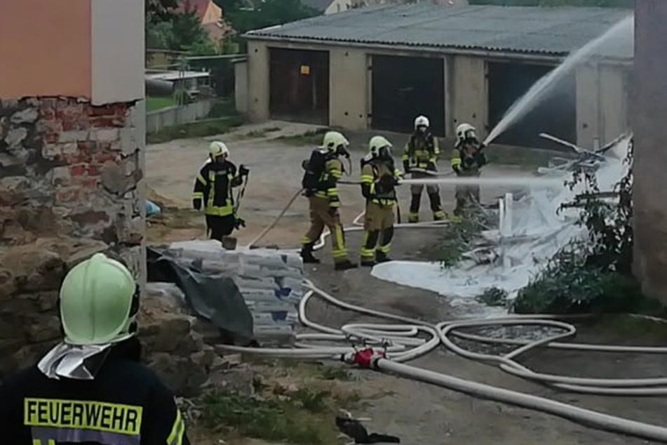Brenzlige Situation: Holzstapel-Brand droht auf Gebäude überzugreifen