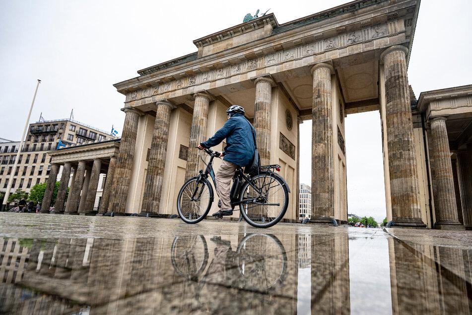 Ein Mann fährt auf seinem Fahrrad am Brandenburger Tor vorbei. Auch zum Ende der Woche könnte es in der Hauptstadt nass werden.