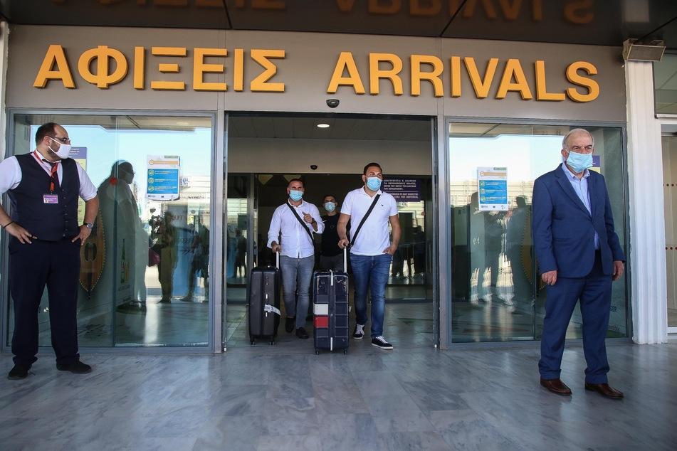 Touristen mit medizinischem Mundschutz kommen am internationalen Flughafen der griechischen Insel Kreta an. Landesweit wurden alle Flughäfen für Auslandsflüge geöffnet. Erstmals nach Ausbruch der Corona-Pandemie sind Charterflugzeuge aus Deutschland auf dem Flughafen von Kreta gelandet und wurden feierlich mit Musikanten und den lokalen Schnaps Tsikoudiá empfangen.