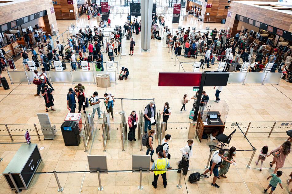 Fluggäste warten in der Haupthalle des Flughafens Berlin-Brandenburg. Der BER hat bei einer Umfrage unter den Fluggästen besser abgeschnitten als der ehemalige Flughafen Tegel.