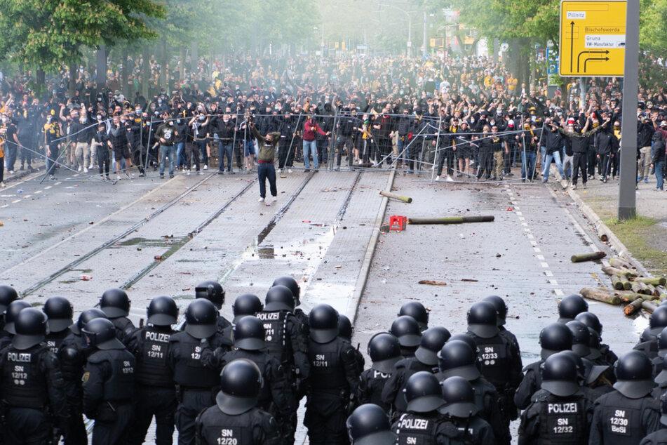 Die Polizei steht vor dem Stadion Fans gegenüber.