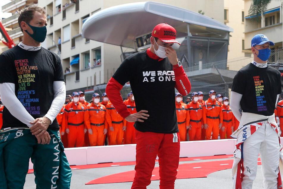 Ferrari-Pilot Charles Leclerc (M.) aus Monaco steht mit Haas-Pilot Mick Schumacher (r.) und Aston-Martin-Pilot Sebastian Vettel aus Deutschland während der Zeremonie vor dem Start des Großen Preises von Monaco auf der Rennstrecke.