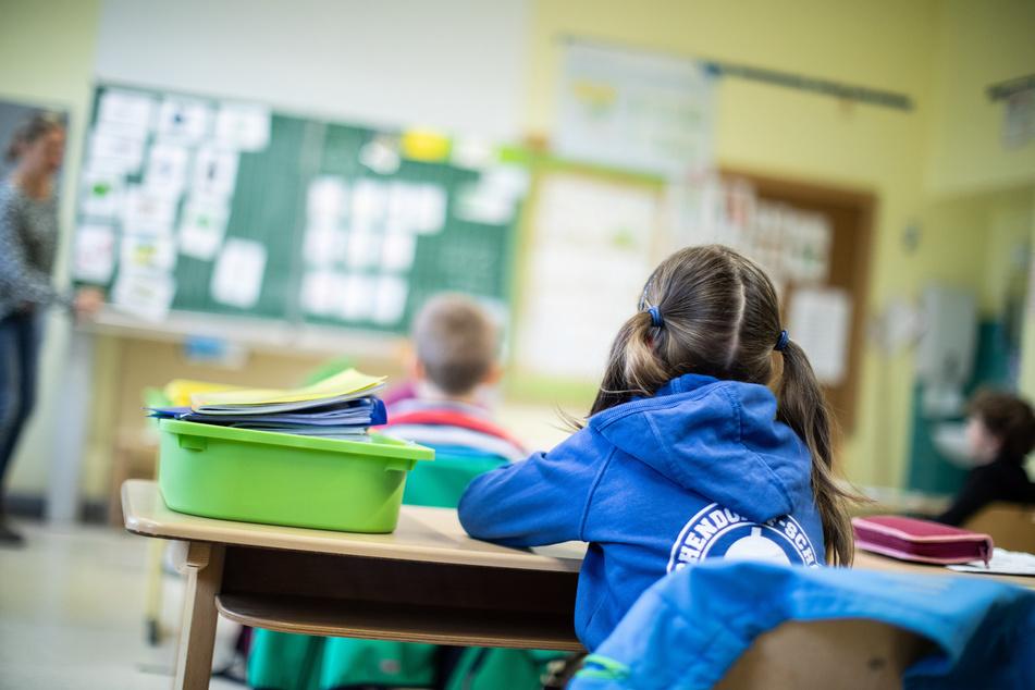 Schülerinnen und Schüler einer Grundschule sitzen mit Abstand in ihrem Klassenraum. In Sachsen können an diesem Mittwoch wegen sinkender Infektionszahlen weitere Schulen und Kitas öffnen.
