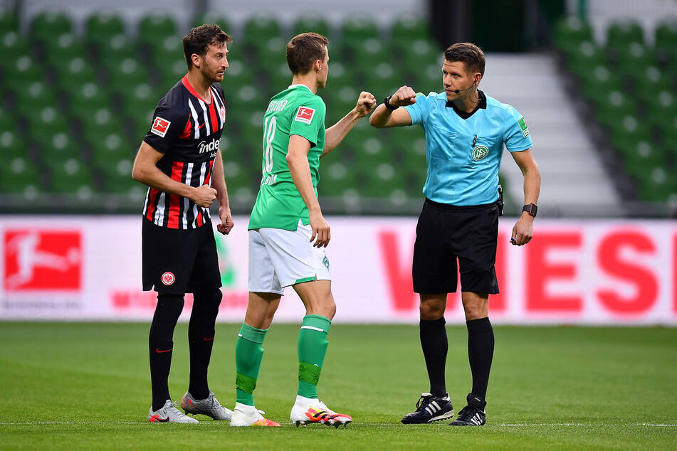 Eintracht Frankfurts Kapitän David Abraham (l.), Bremens Niklas Moisander (m.) und Schiedsrichter Patrick Ittrich.