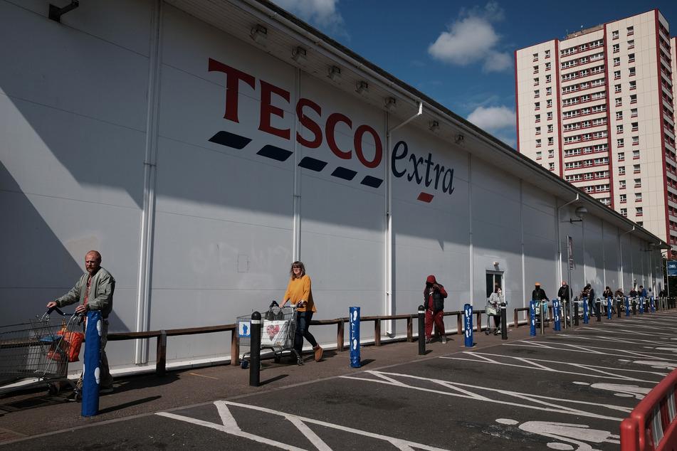 Kunden stehen in London mit Einkaufswagen und großem Abstand zueinander in einer Warteschlange des Supermarktes Tesco. Wegen des Verkaufs von Lebensmitteln, deren Haltbarkeitsdatum abgelaufen war, wurde der britische Handelsriese zu einer Millionenstrafe verdonnert.