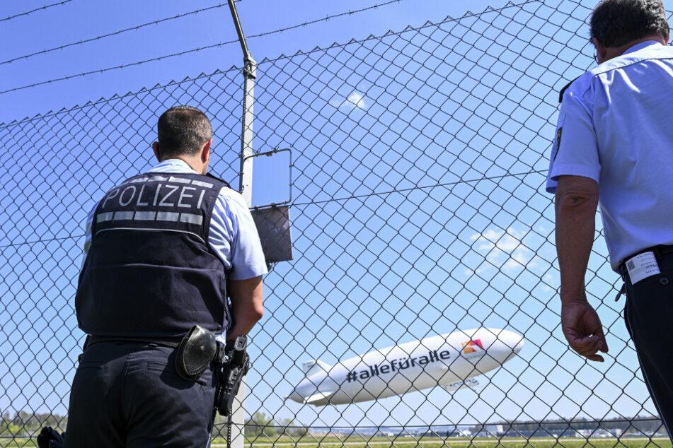 Friedrichshafen: Zwei Polizisten verfolgen vom Zaun aus den Start des Zeppelin NT (Neue Technik).
