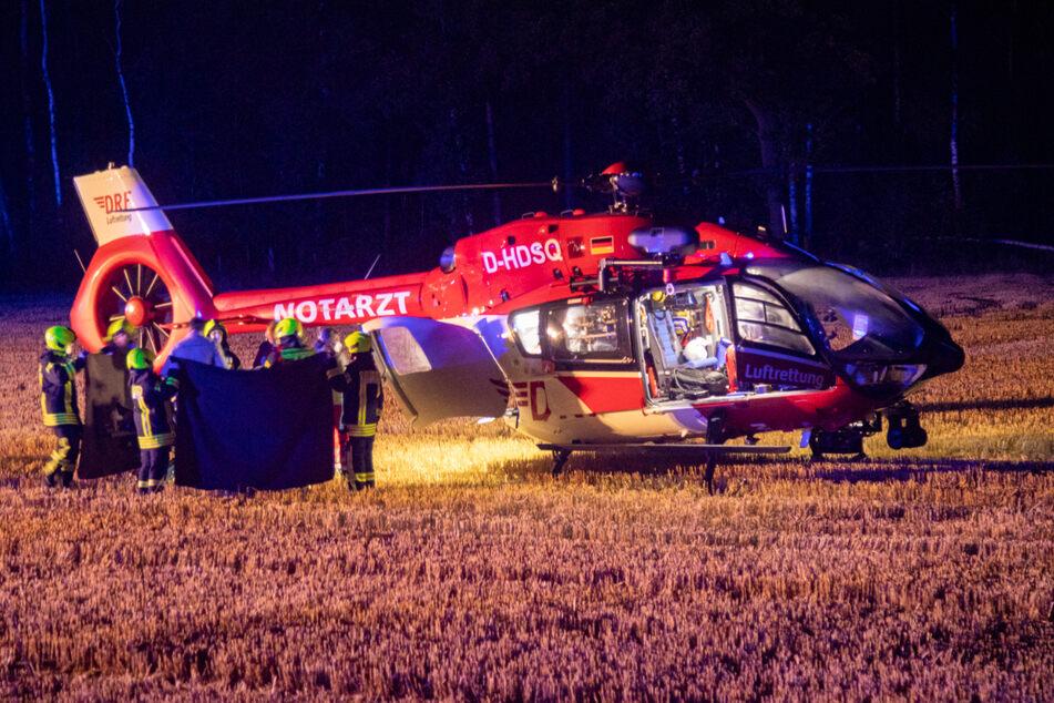 Feuerwehrmänner bringen den schwerverletzten Radfahrer zum Hubschrauber.