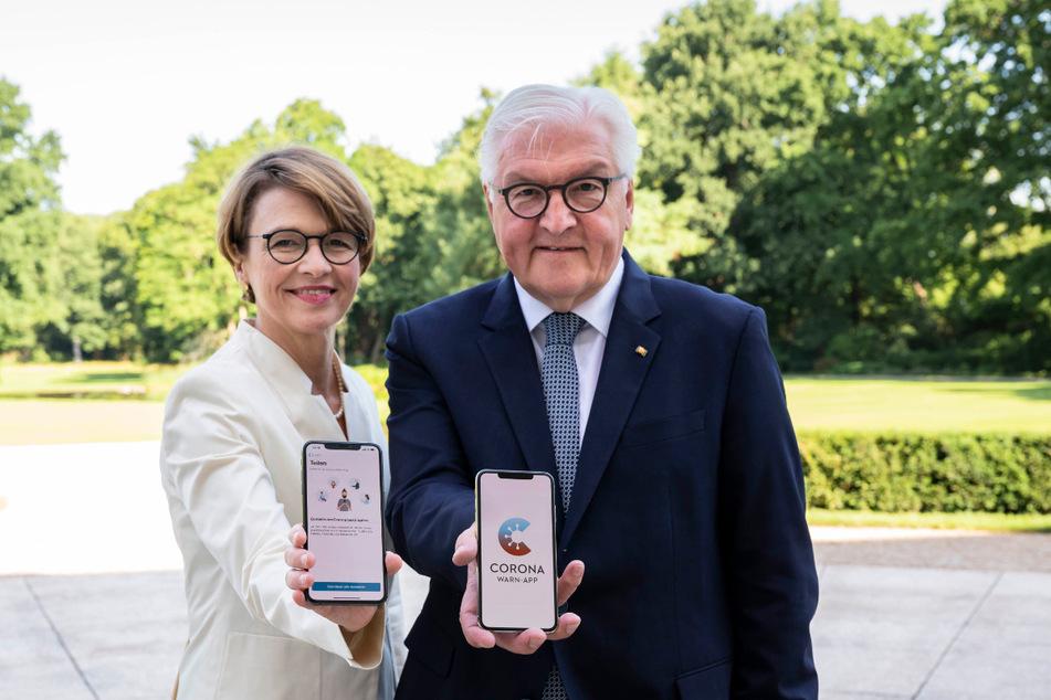 Bundespräsident Frank-Walter Steinmeier und Elke Büdenbender mit der Corona-Warn-App der Bundesregierung im Park von Schloss Bellevue in Berlin.