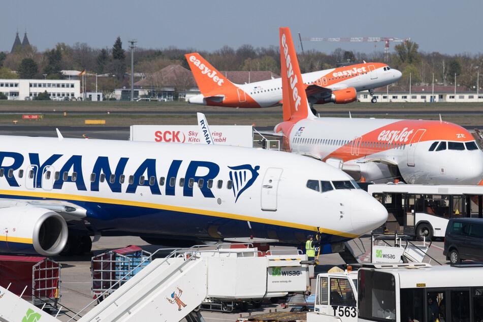 Flugzeuge der Gesellschaften Ryanair und Easyjet stehen auf dem Flughafen Tegel, während im Hintergrund eine Maschine gerade startet.