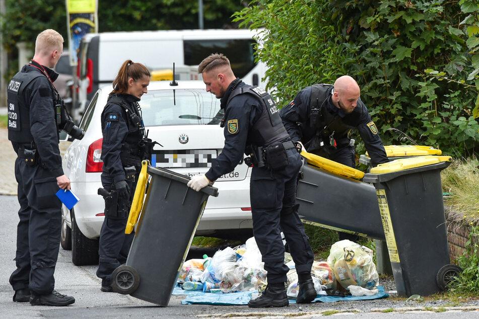 Eine Mülltonne nach der anderen entleerten die Polizisten am Donnerstag auf der Suche nach Hinweisen auf den Täter von Großröhrsdorf.