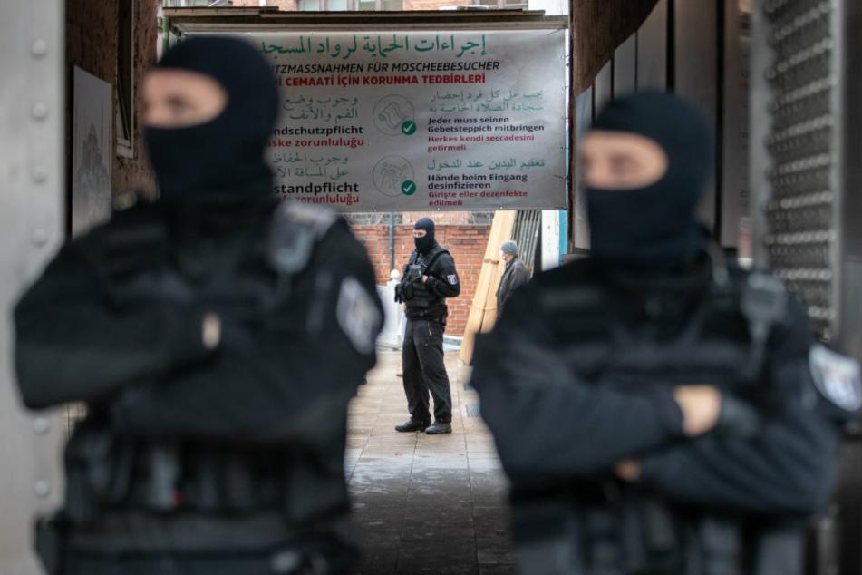 Im Vordergrund stehen zwei Polizisten am Eingang zur Moschee. Im Hintergrund ist ein Plakat zu erkennen, welches die Besucher in drei Sprachen über die geltenden Schutzmaßnahmen informiert.
