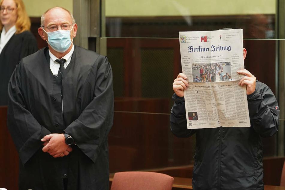 Jens F. (56, r.) steht am ersten Prozesstag neben seinem Verteidiger Friedrich Humke und hält sich eine Zeitung vor das Gesicht, um nicht erkannt zu werden.