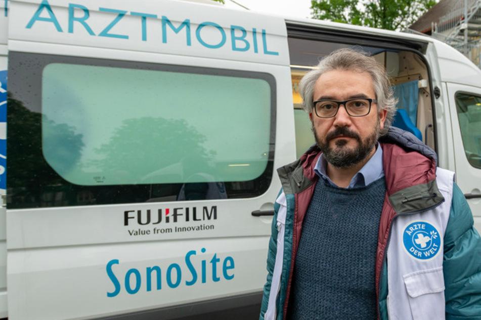 """Cevat Kara, Projektleiter bei """"Ärzte der Welt"""" steht vor einem weißen Behandlungsbus der Organisation """"Ärzte der Welt""""."""