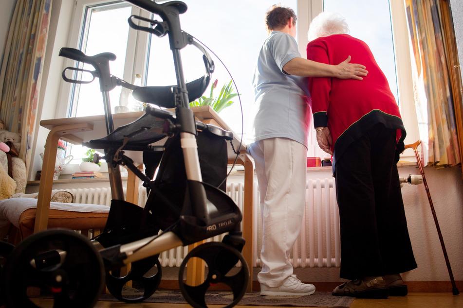 Eine Pflegerin und eine Bewohnerin des Pflegeheims schauen zusammen aus einem Fenster eines Pflegeheims.