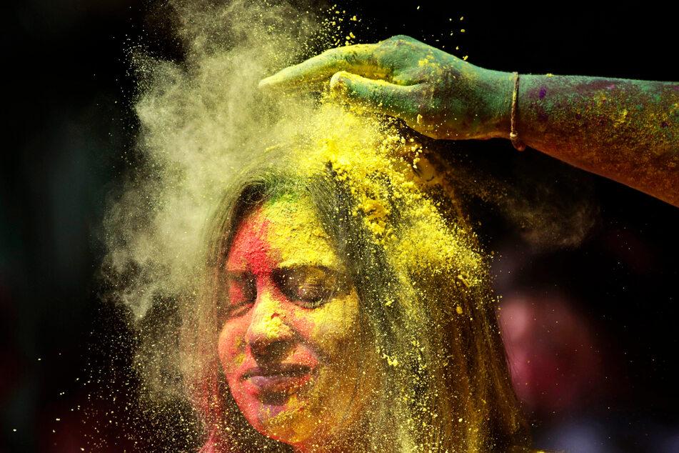 Ein Mann beschmiert das Gesicht einer Frau während der Feierlichkeiten zum Holi-Fest in Mumbai mit farbigem Puder.