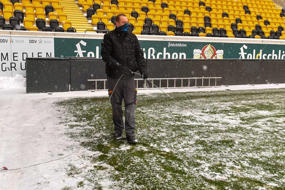 Mit einem dünnen Stahlseil fährt Platzwart Axel Hocke über den Platz, um den Schnee richtig ins Gras zu drücken. Dann kann er besser abtauen.