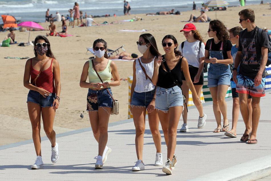 Menschen in Biarritz, Südwestfrankreich, tragen Mundschutz, während sie am Strand spazieren. Mundschutzmasken sind jetzt in Frankreichs Supermärkten, Einkaufszentren, Banken, Geschäften und Markthallen Pflicht.